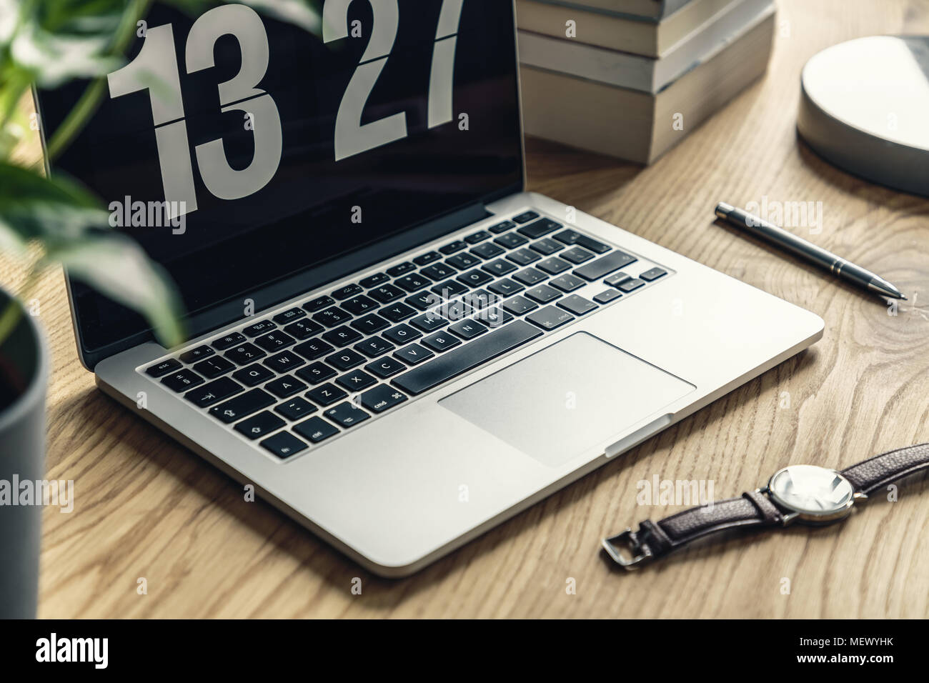 Close-up of a laptop showing time, watch, pen and books on a wooden desk Stock Photo