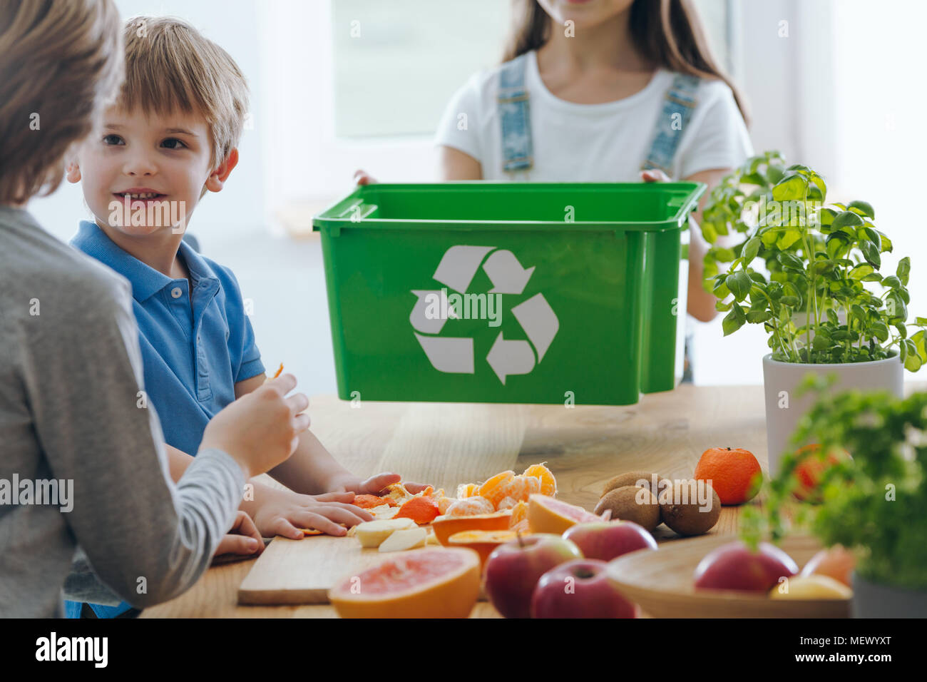 Kids in the kitchen throwing out fruit remains into a green bin for biodegradable waste - Stock Image
