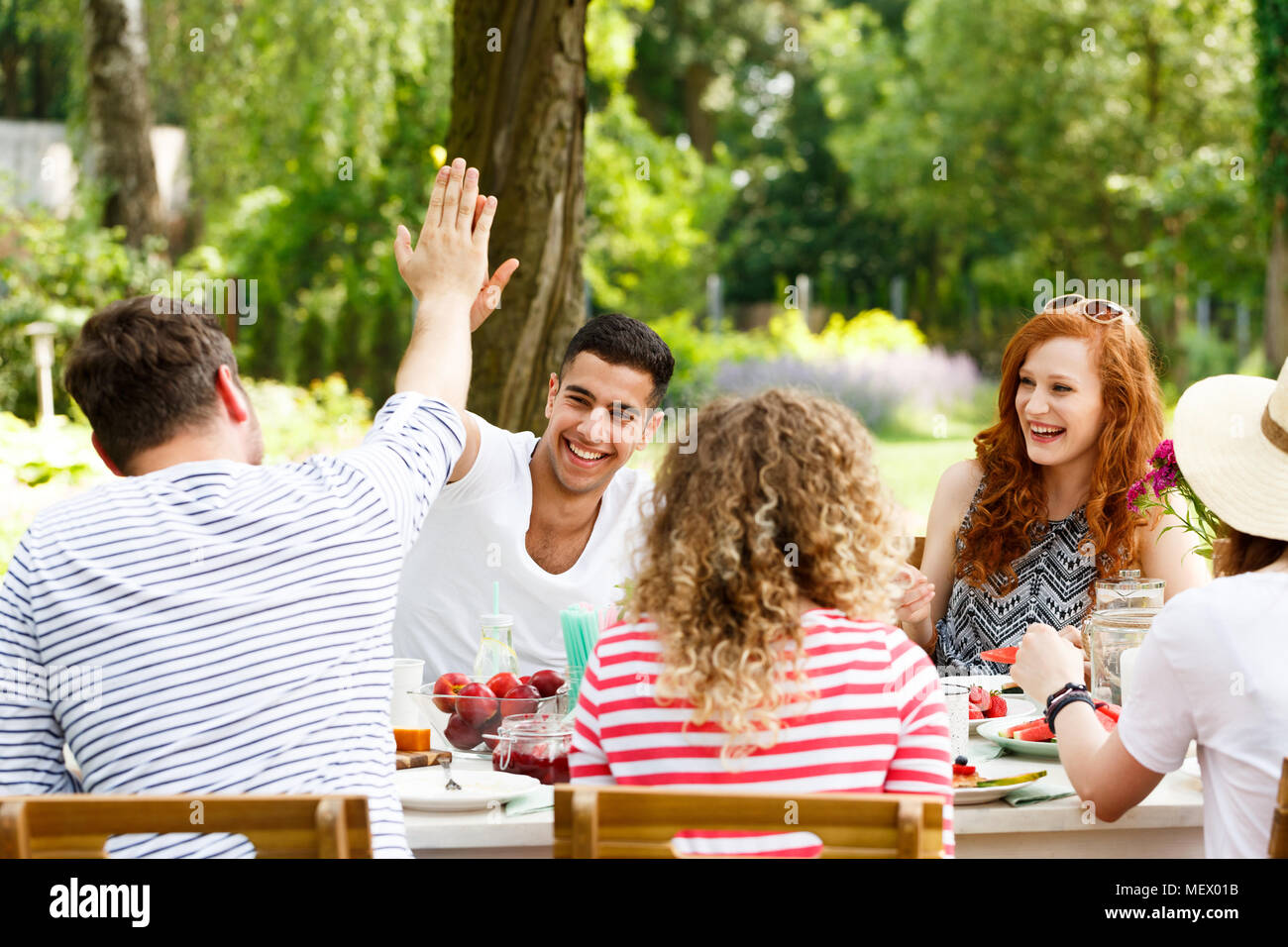 Smiling group of young people having fun, laughing and eating healthy food outside - Stock Image