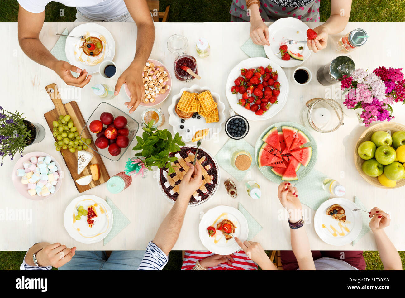 Multicultural group sharing healthy food like fruit and cheese outside with flowers on the table - Stock Image