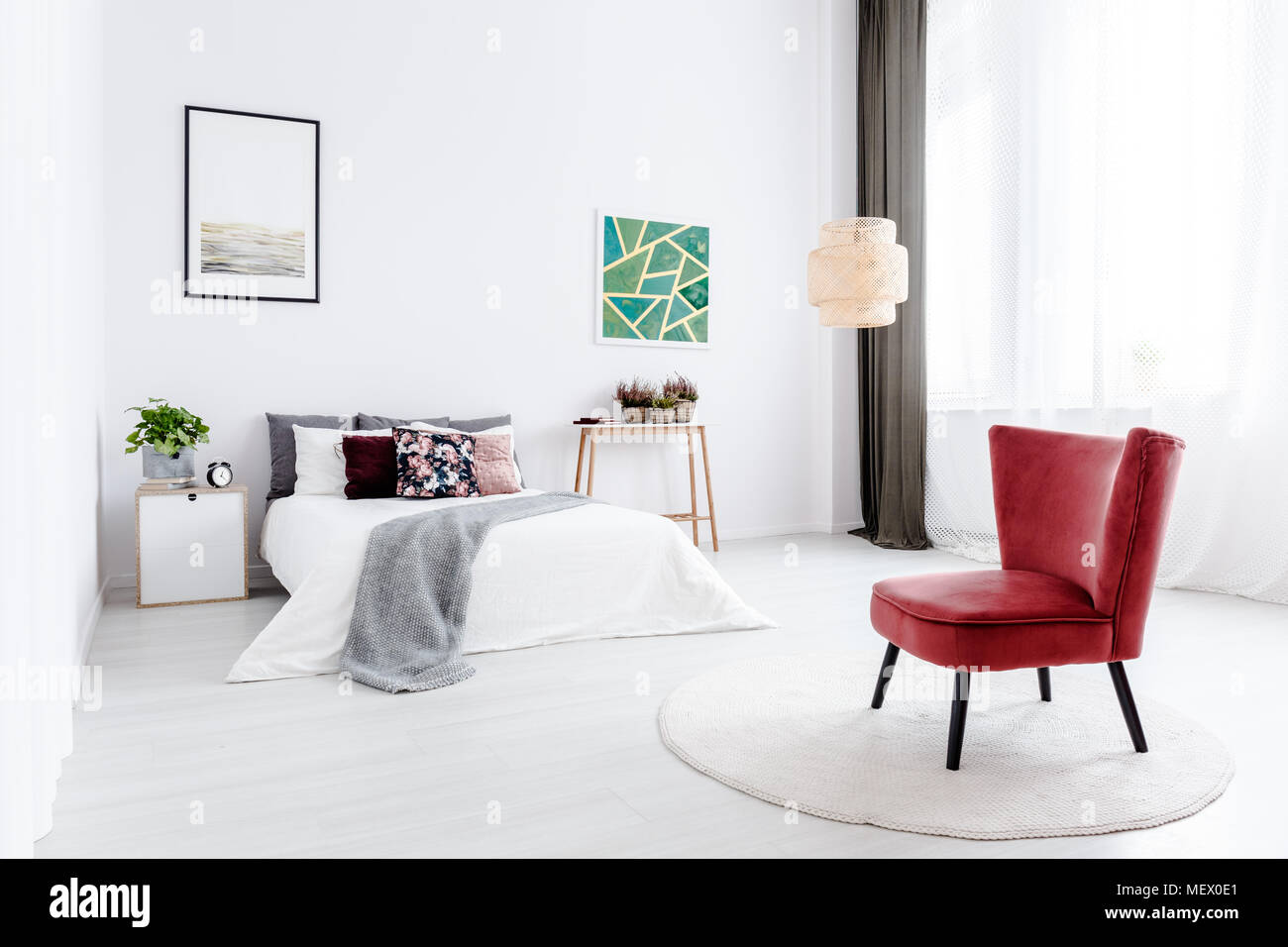 Red armchair on round rug in white bedroom interior with green ...