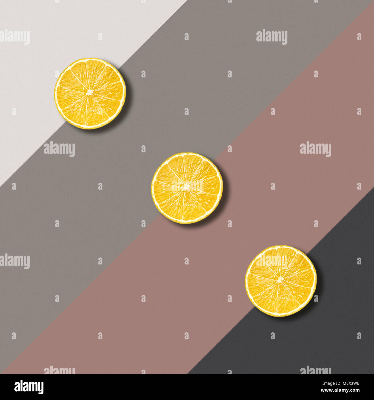 Abstract image with three lemon slices on color background, minimalist geometric food photography - Stock Image