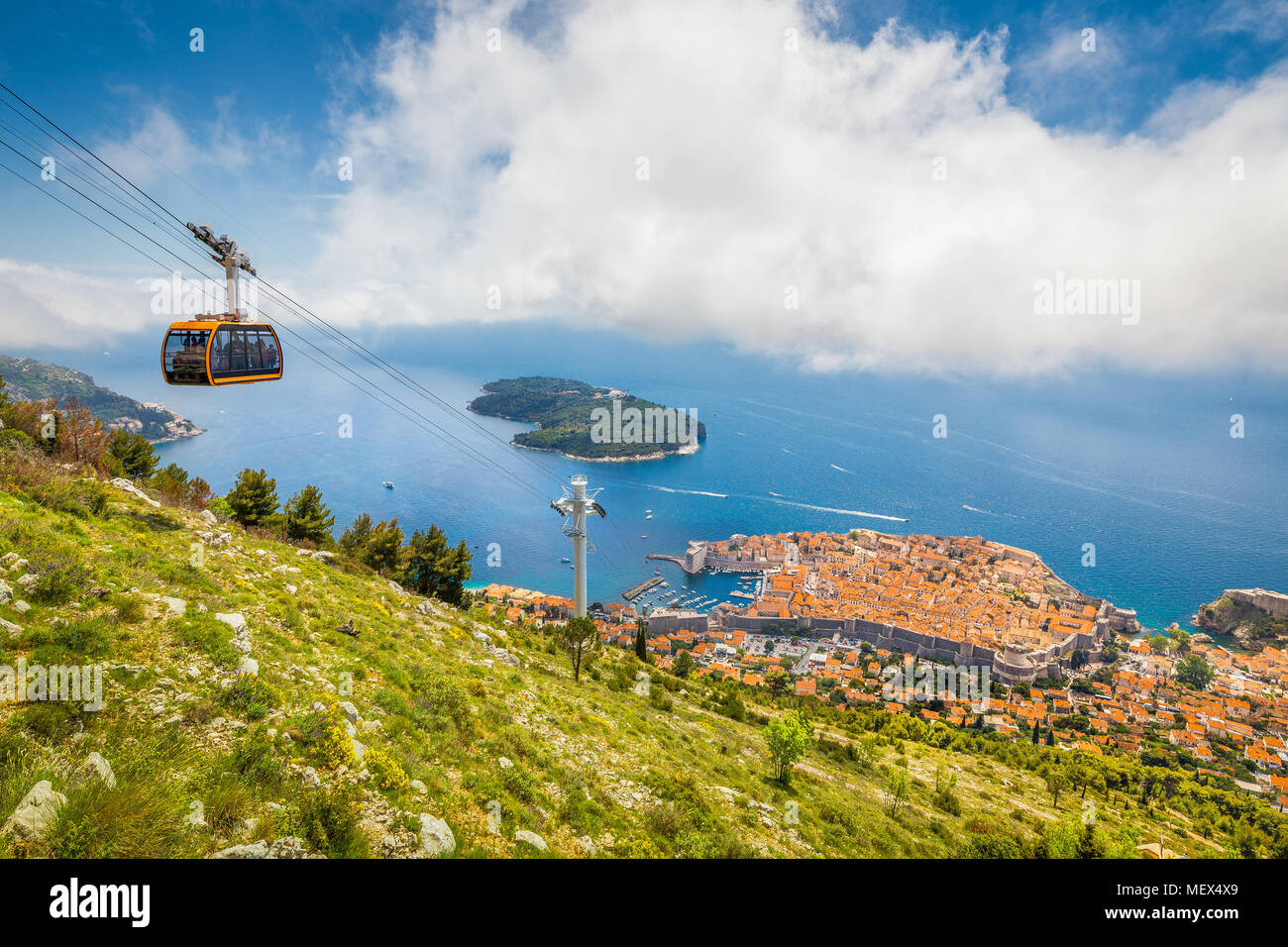 Aerial panoramic view of the old town of Dubrovnik with famous Cable Car on Srd mountain on a sunny day with blue sky and clouds in summer, Croatia - Stock Image