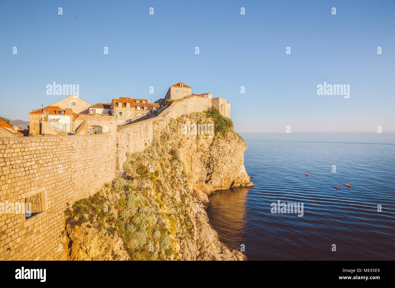 Panoramic view of the old town of Dubrovnik with calm sea in beautiful golden evening light at sunset with blue sky in summer, Dalmatia, Croatia - Stock Image