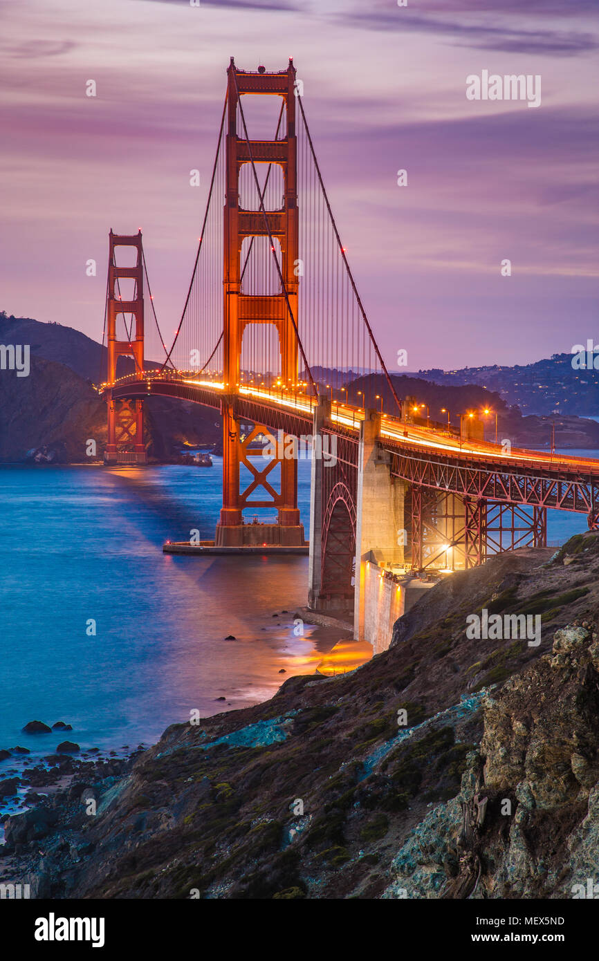 Classic panorama view of famous Golden Gate Bridge seen from scenic Baker Beach in beautiful post sunset twilight with blue sky and clouds at dusk - Stock Image