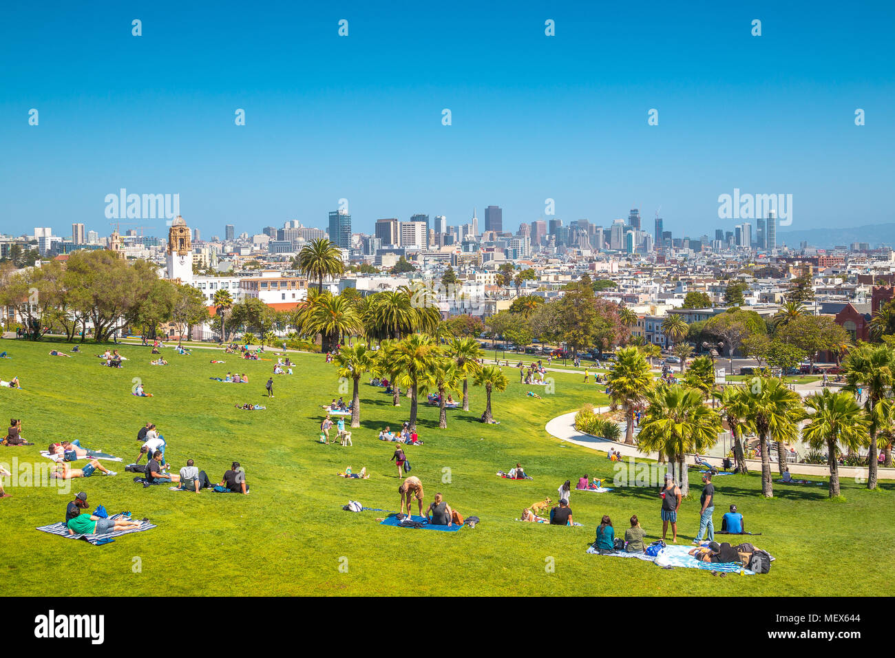 People enjoying the sunny weather on a beautiful day with clear blue skies with the skyline of San Francisco in the background, California, USA - Stock Image