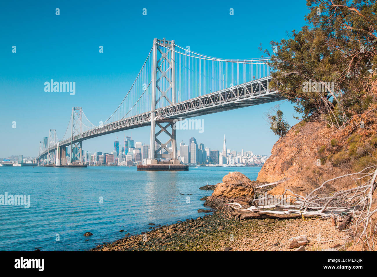 Classic panoramic view of San Francisco skyline with famous Oakland Bay Bridge illuminated on a sunny day with blue sky in summer, San Francisco - Stock Image
