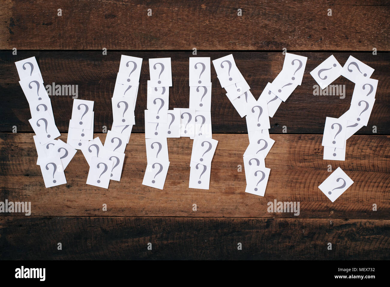 white paper note with question mark arranged to make a WHY word on wooden table. WHY concept background - Stock Image