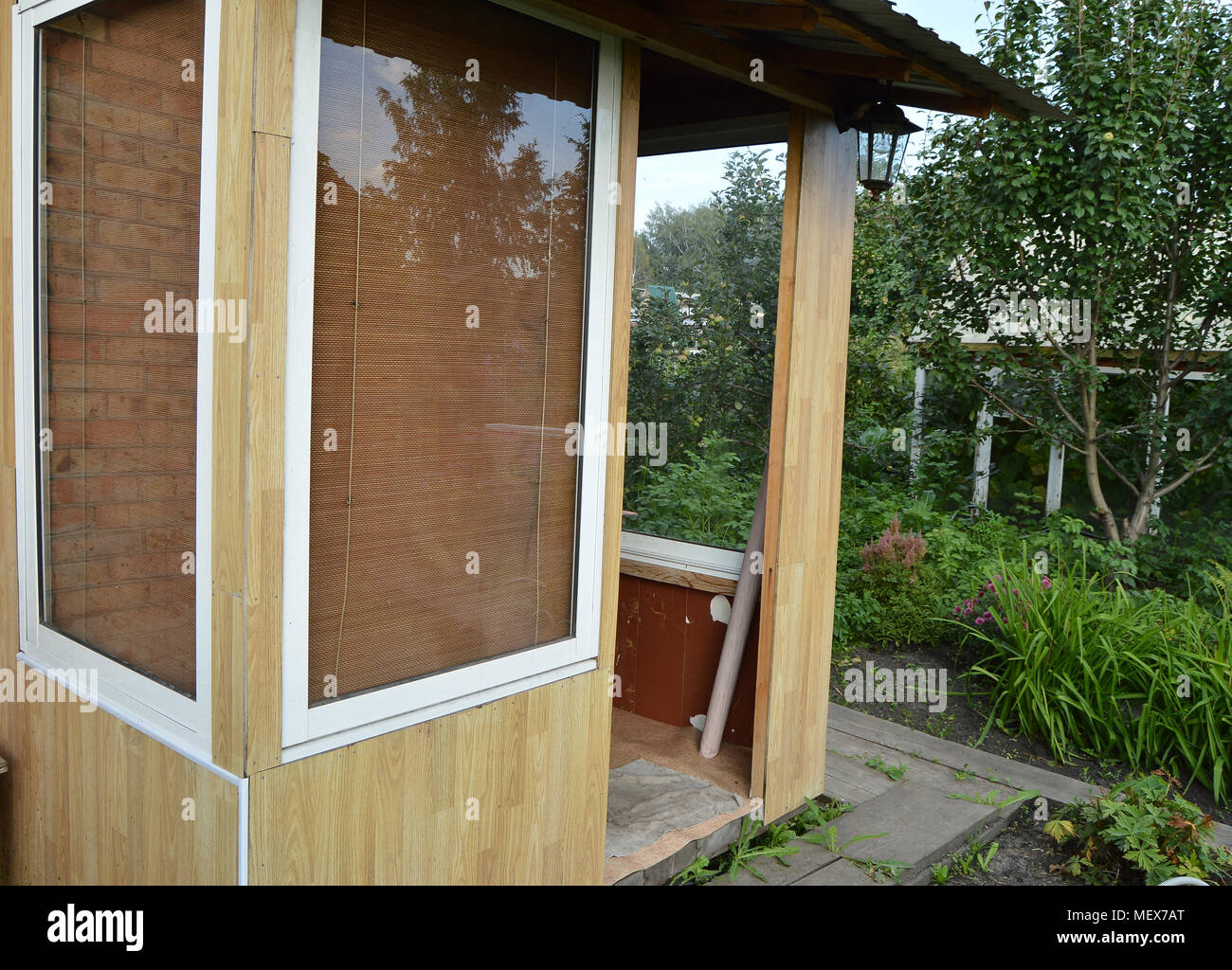 Glass doors and Windows in a wooden veranda. Entrance to the country house Stock Photo