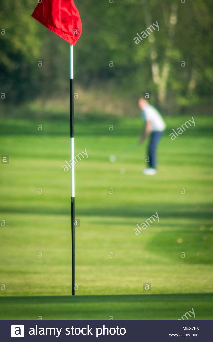 A golfer, out of focus in the background, prepares to play his shot towards the flag, in focus in the forground. portrait orientation - Stock Image
