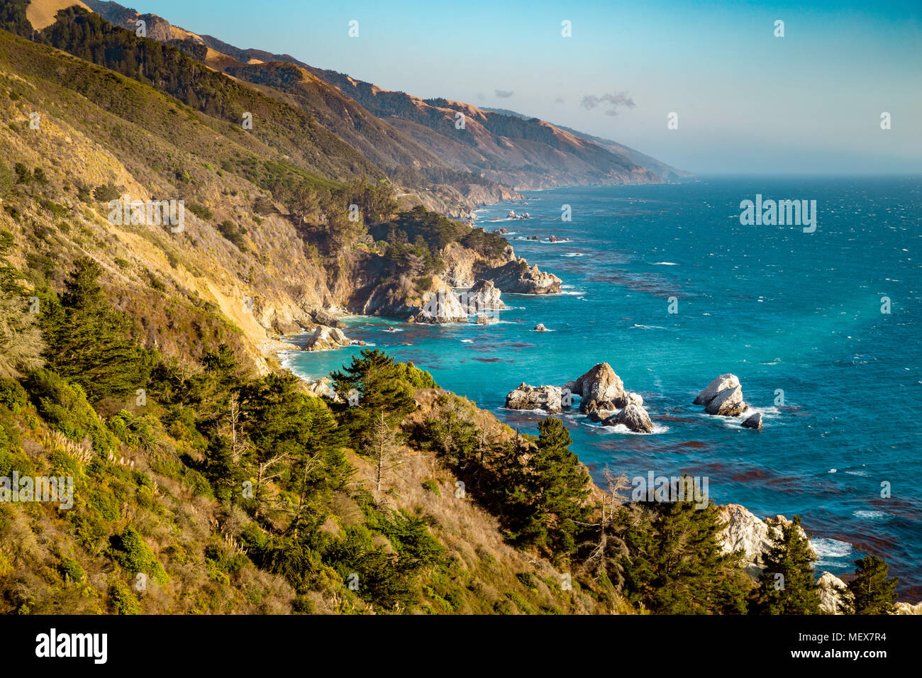 Scenic view of the rugged coastline of Big Sur with Santa Lucia Mountains along famous Highway 1 illuminated in evening light at sunset, California Stock Photo