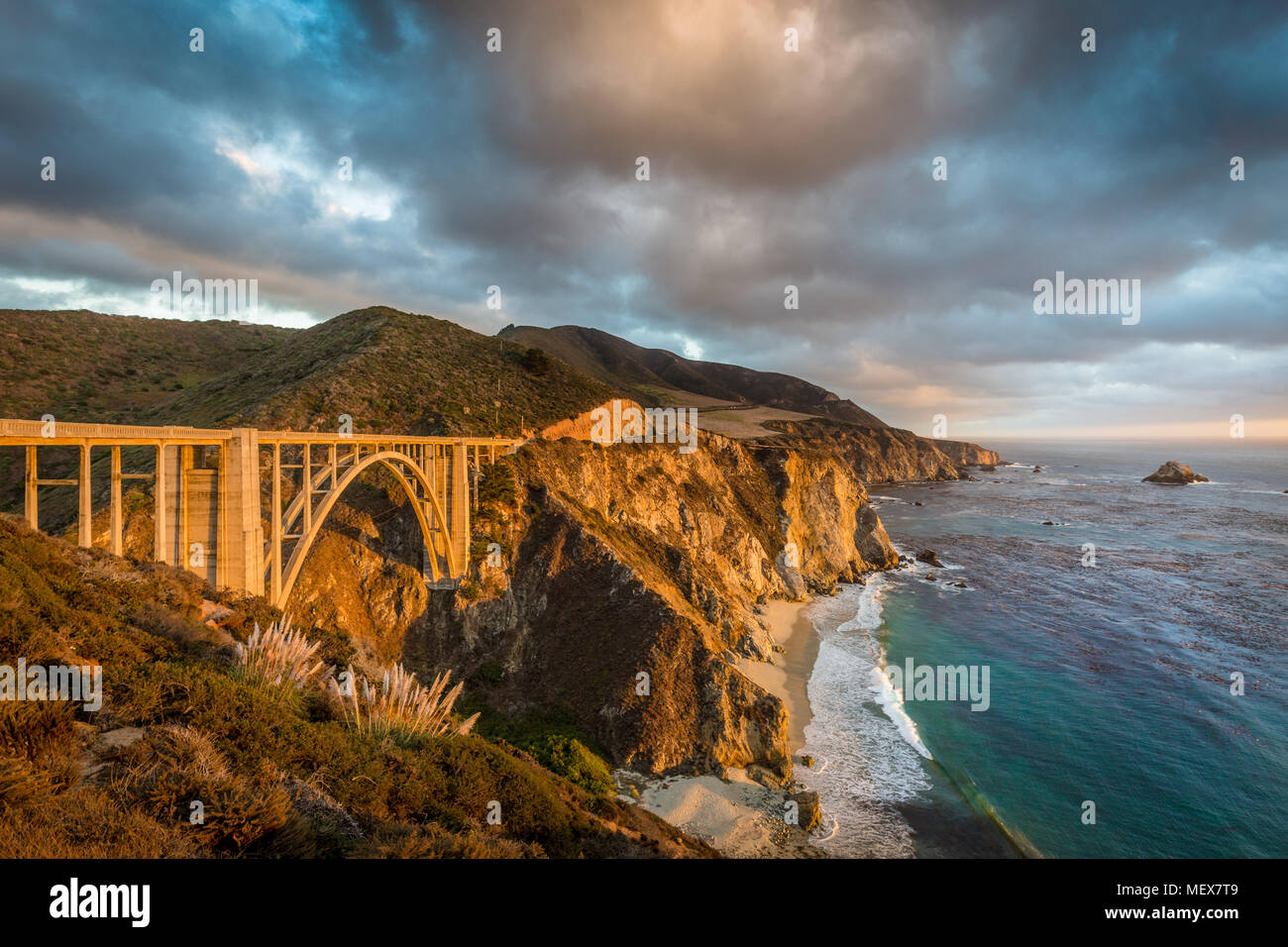 Scenic panoramic view of historic Bixby Creek Bridge along world famous Highway 1 in beautiful golden evening light at sunset with dramatic cloudscape - Stock Image
