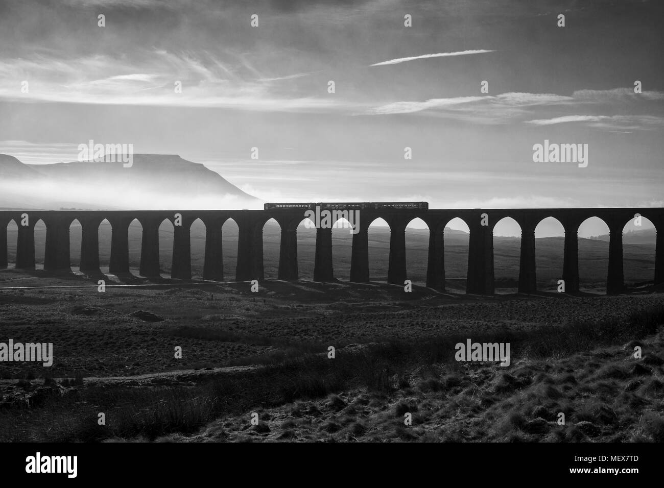A Northern rail class 153 + 156 sprinter trains cross Ribblehead viaduct on the Settle to Carlisle railway with a misty Ingleborough behind - Stock Image