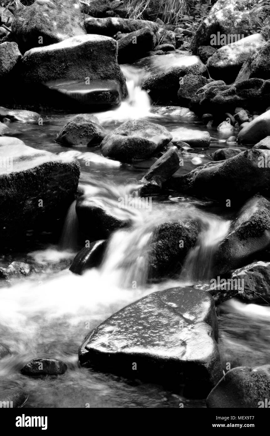 Misted water flowing through a Mountain rock riverbed in black and white - Stock Image
