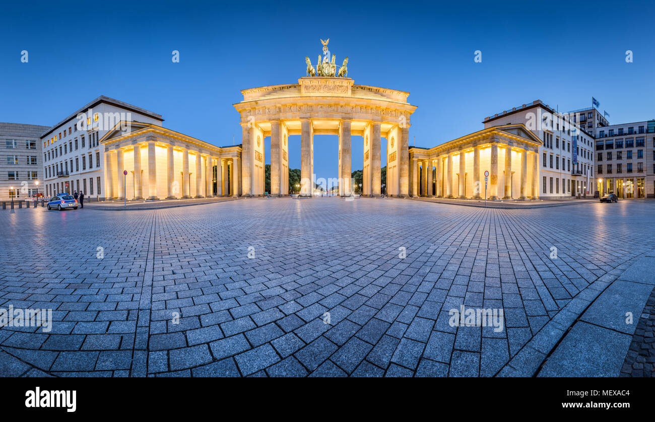 Classic panoramic view of famous Brandenburg Gate illuminated during blue hour at dusk, central Berlin Mitte, Germany - Stock Image