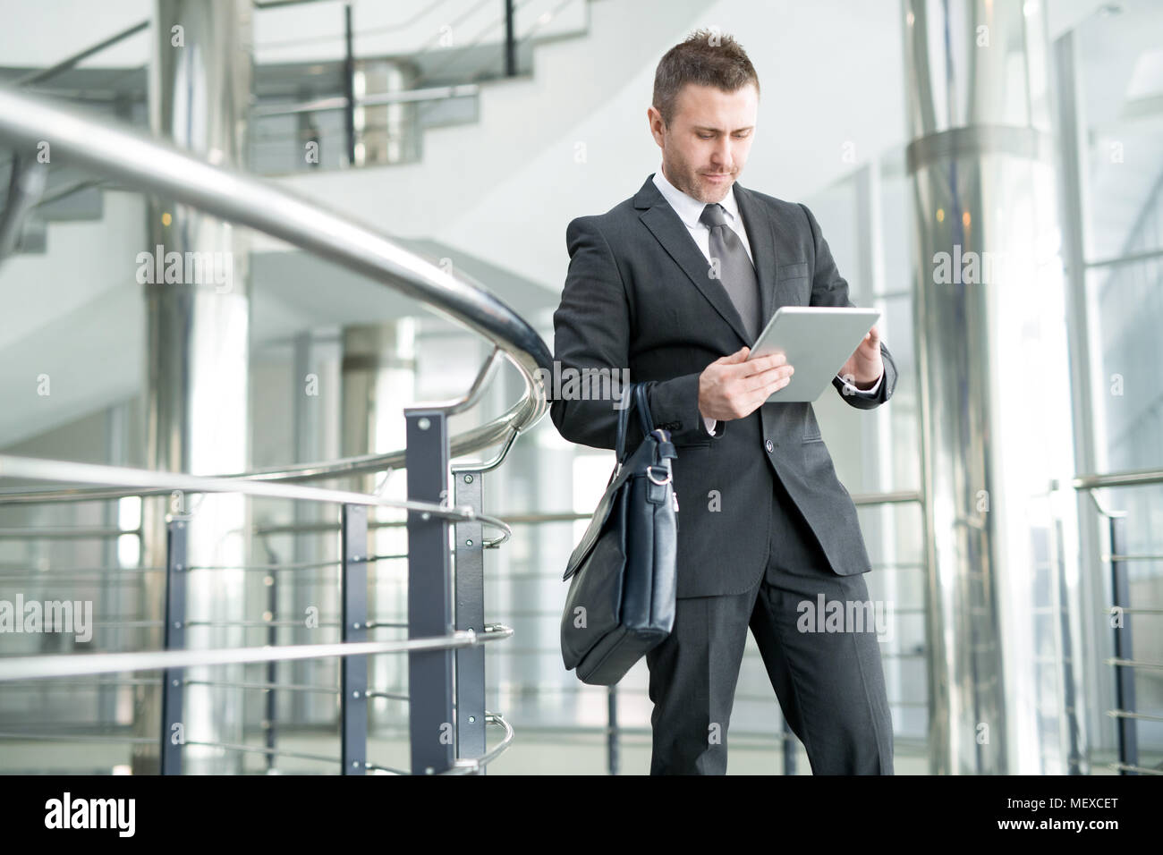 Modern businessman in office hall of large company - Stock Image