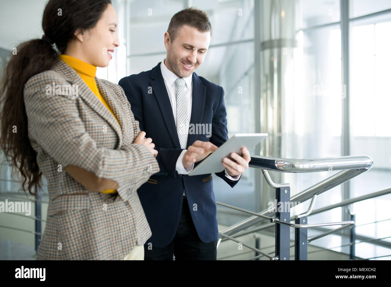 Positive businessman with assistant using tablet Stock Photo