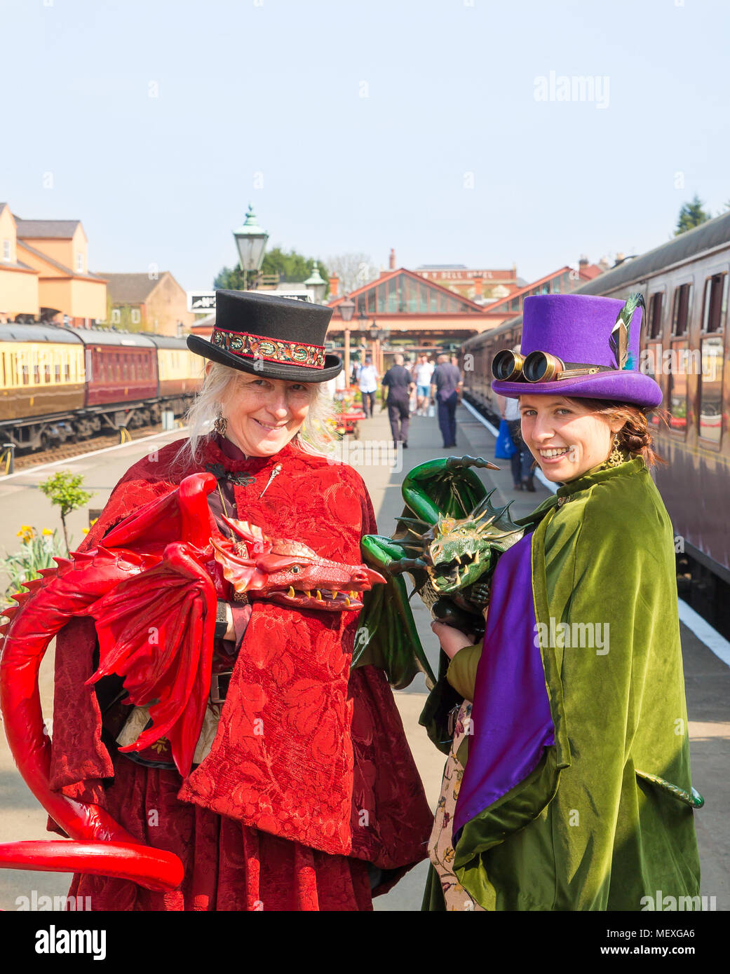 Two smiling females in fancy dress costume with hand-held, life-like dragon puppets on the platform at Kidderminster's Severn Valley Railway station. - Stock Image