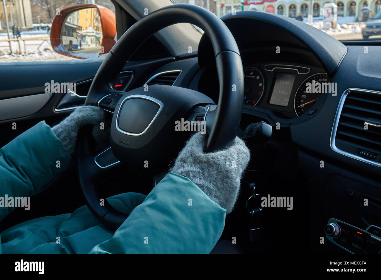 Female hands in the grey mittens on the steering wheel of expensive car - Stock Image