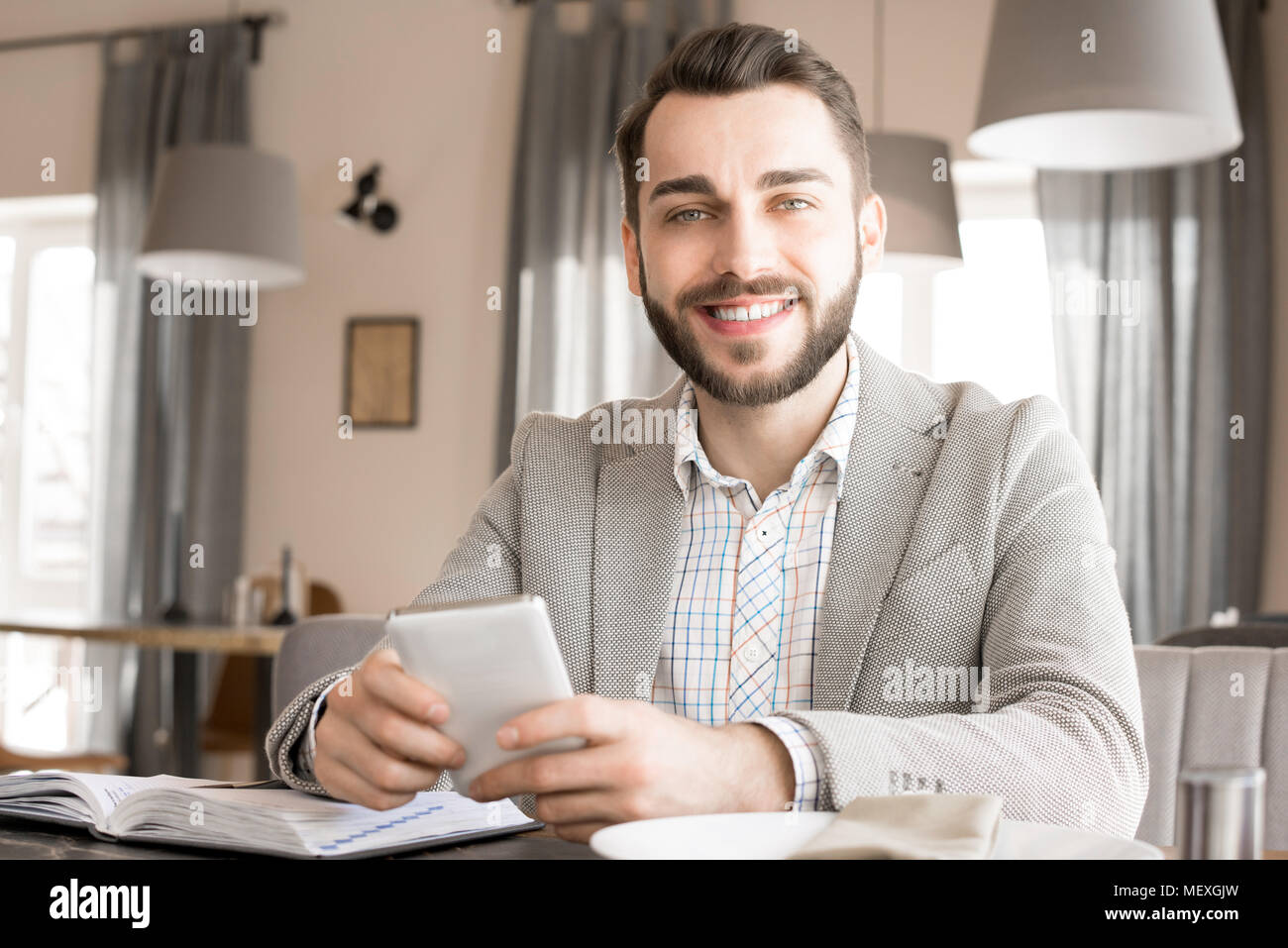 Positive confident entrepreneur in cozy restaurant - Stock Image