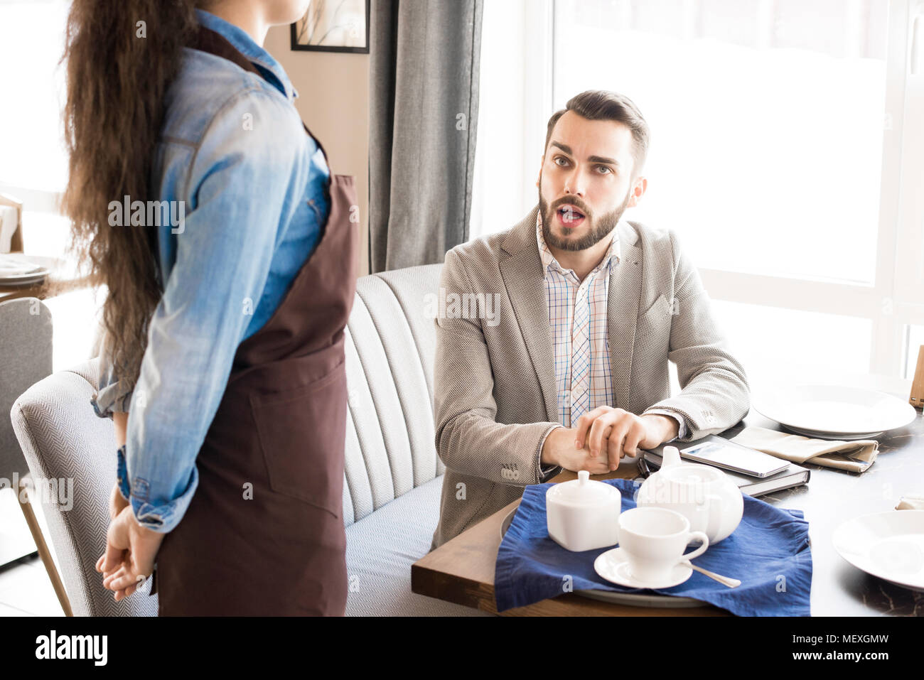 Pensive customer asking waitress in cafe - Stock Image
