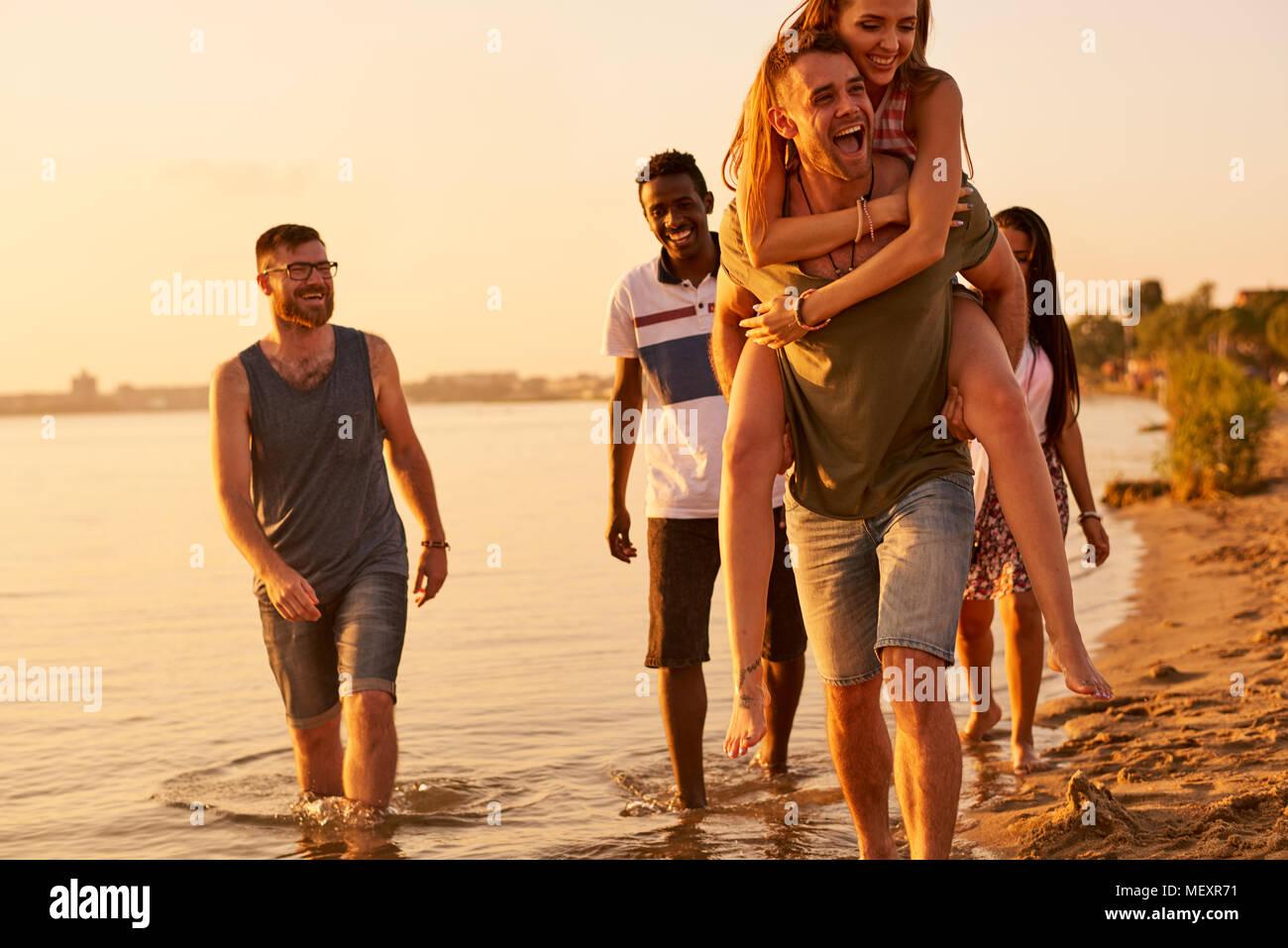 Cheerful friends walking together over coastline - Stock Image