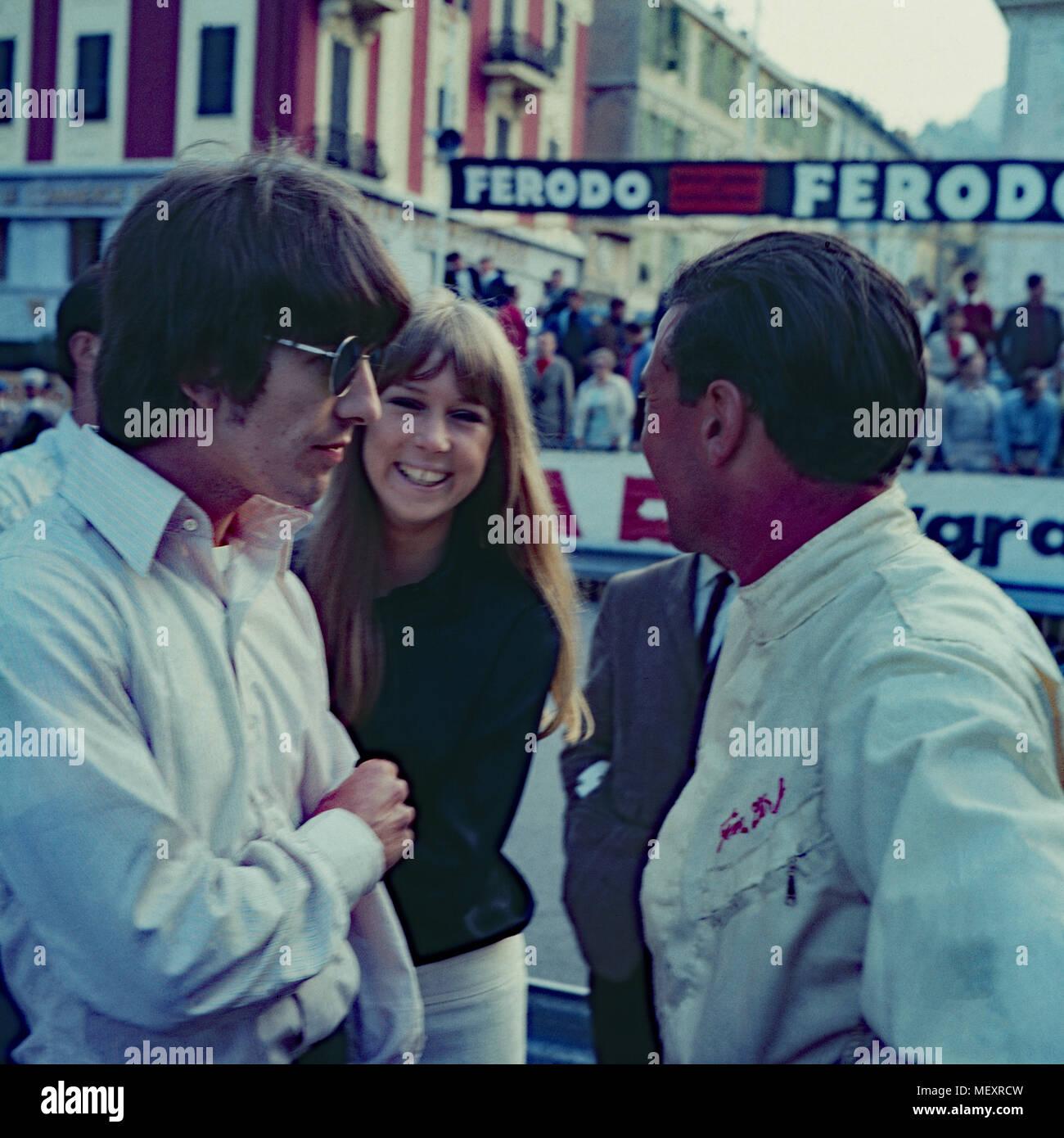 Beatle George Harrison mit Patricia Anne Pattie Boyd im Gespräch mit Rennfahrer Jim Clark bei einem Besuch in Monte Carlo, Monaco 1966. Beatle George Harrison and Patricia Anne Pattie Boyd talking to racing driver Jim Clark while visiting Monte Carlo, Monaco 1966. - Stock Image