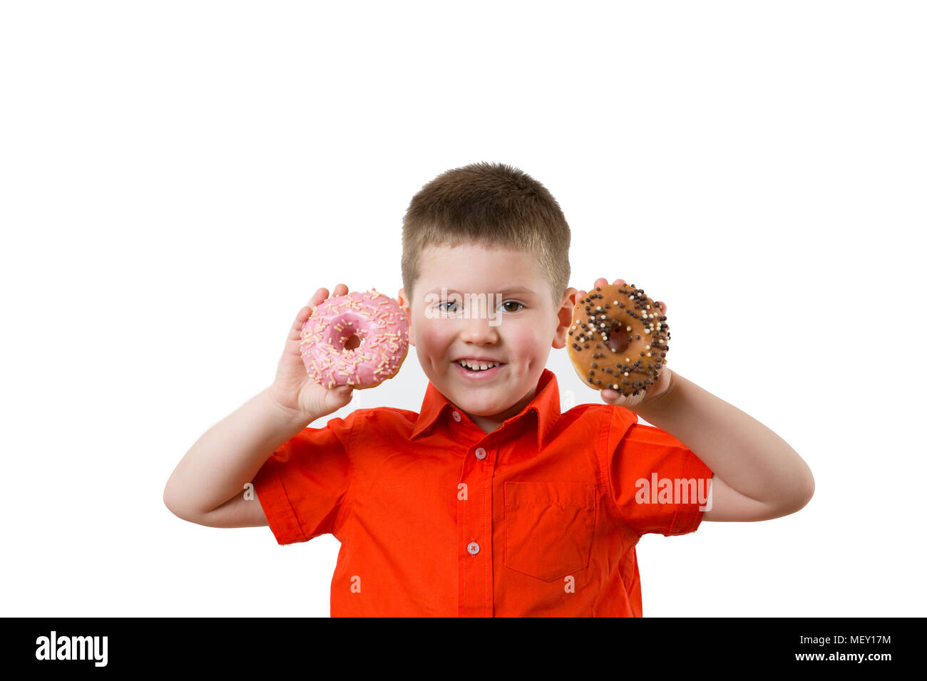Little happy cute boy is eating donut on whte background wall. child is having fun with donut. Tasty food for kids. Funny time at home with sweet food. Bright kid. - Stock Image