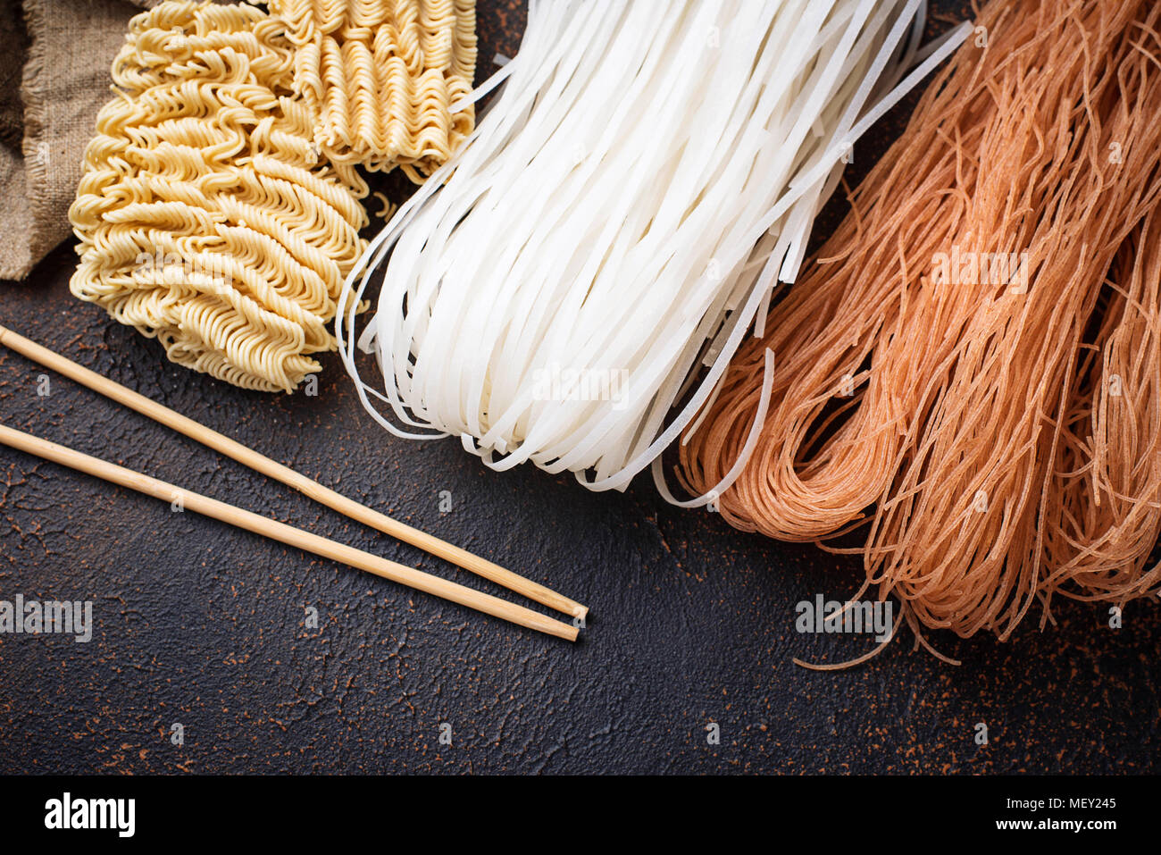 Different Asian rice noodles on rusty background Stock Photo