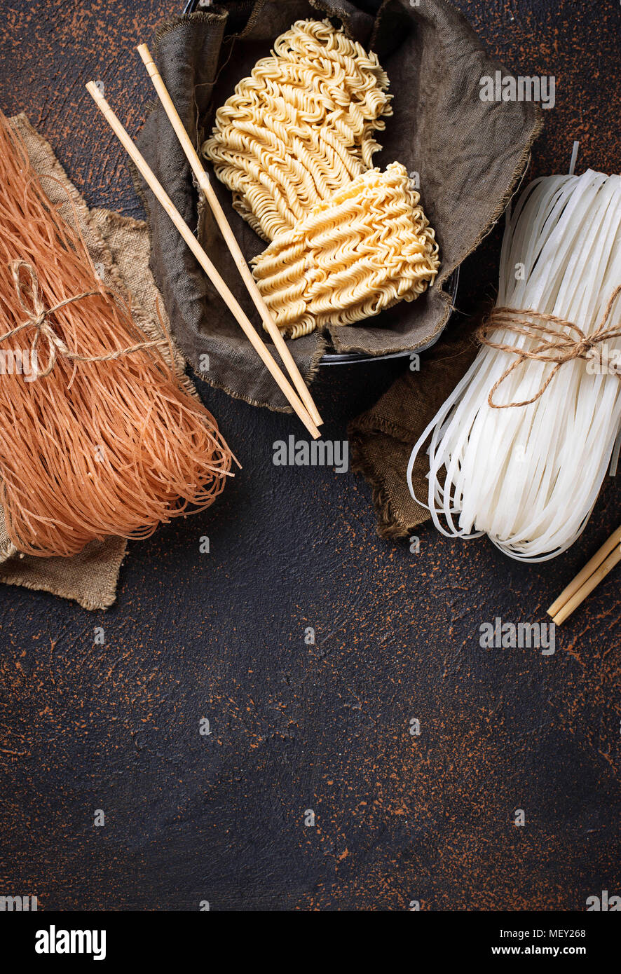 Different Asian rice noodles on rusty background - Stock Image