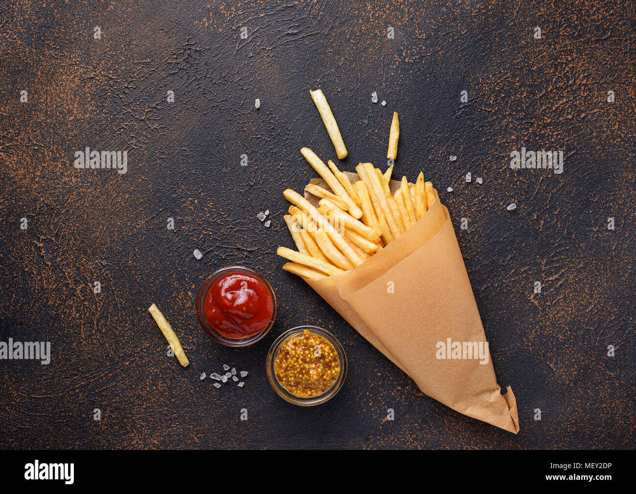French fries in a paper bag with sauces - Stock Image