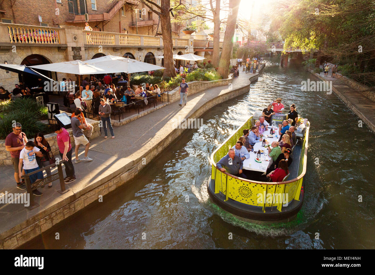 Travellers dine on a barge on the San Antonio river; San Antonio River Walk, San Antonio, Texas USA - Stock Image
