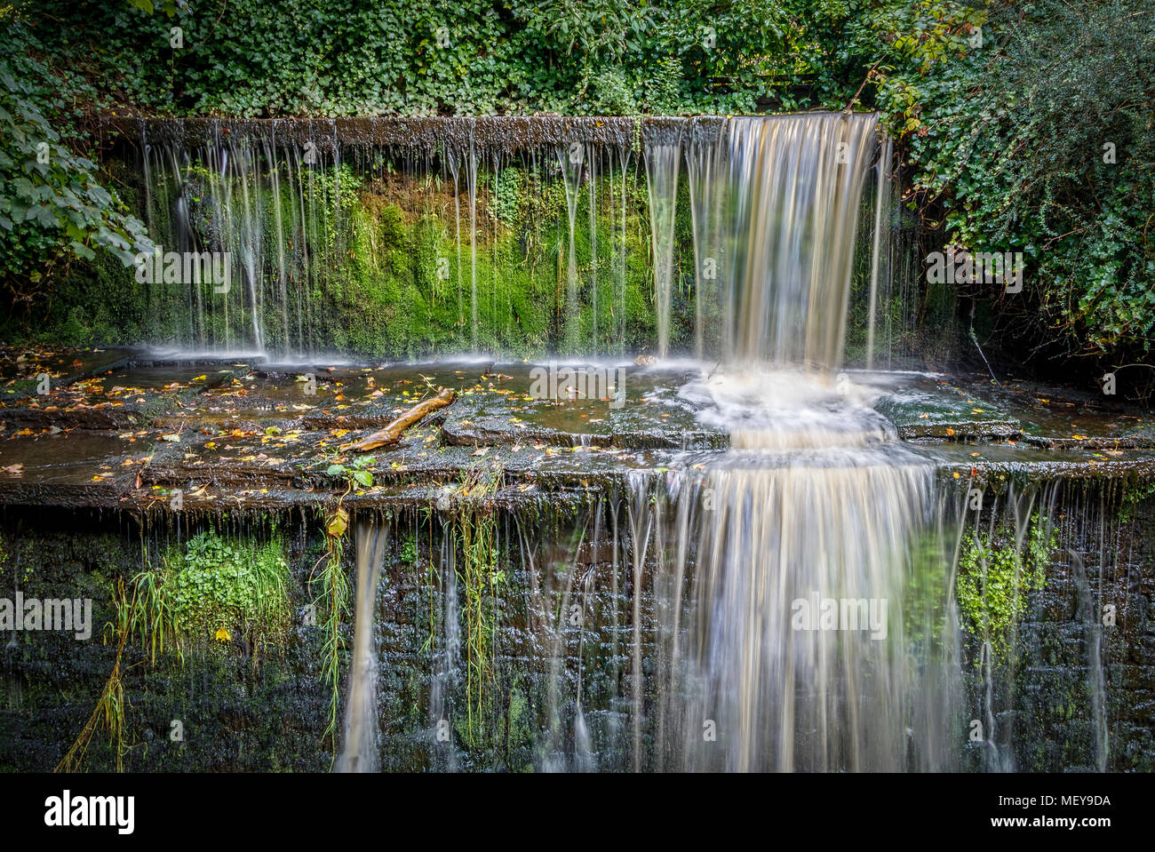Small waterfall over man-made stepped escarpment alongside the Spring Branch Canal in Skipton, North Yorkshire, UK. - Stock Image