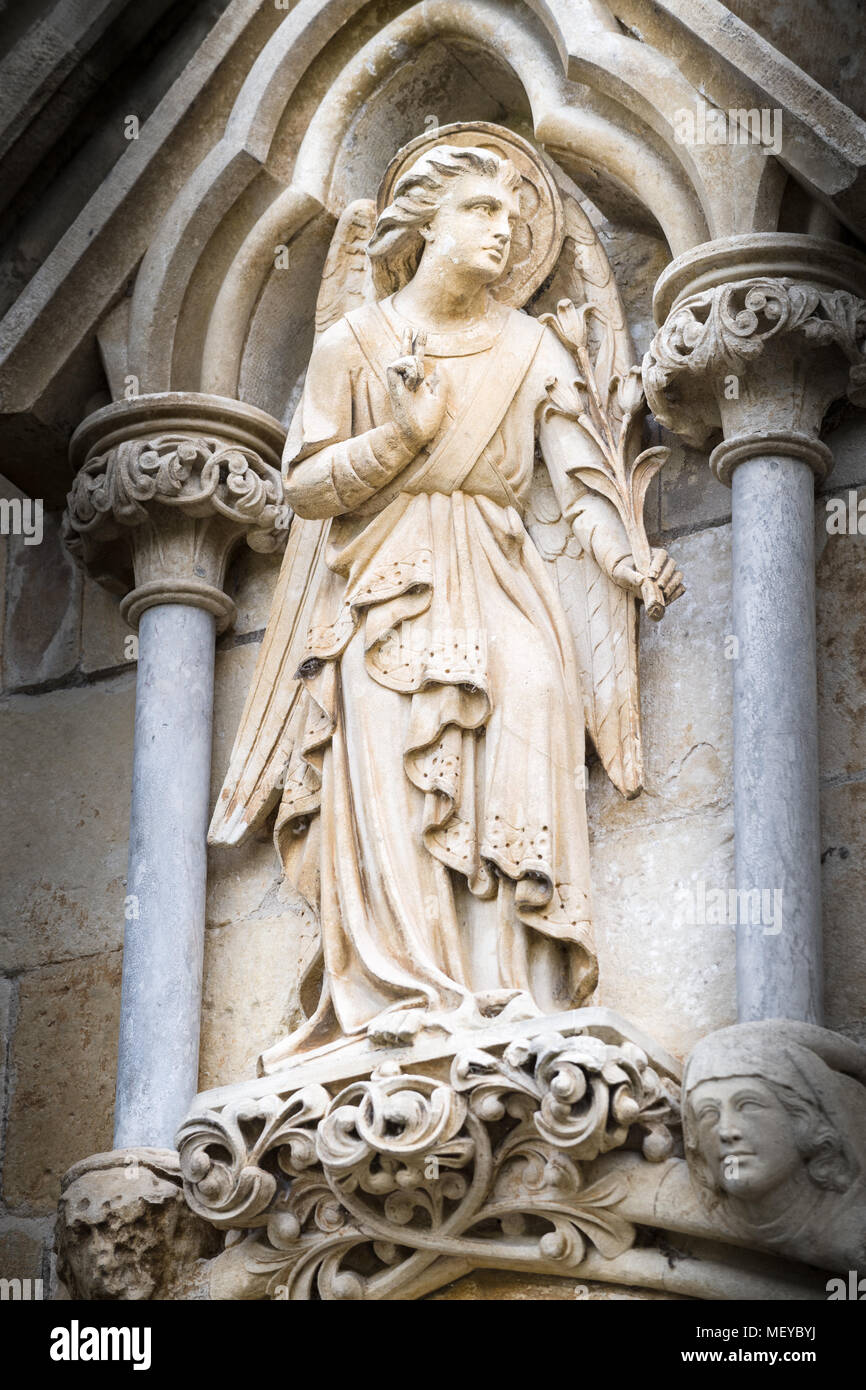 Sculpted stone statue of an angel on the exterior west wall at the medieval cathedral of Salisbury, England. Stock Photo