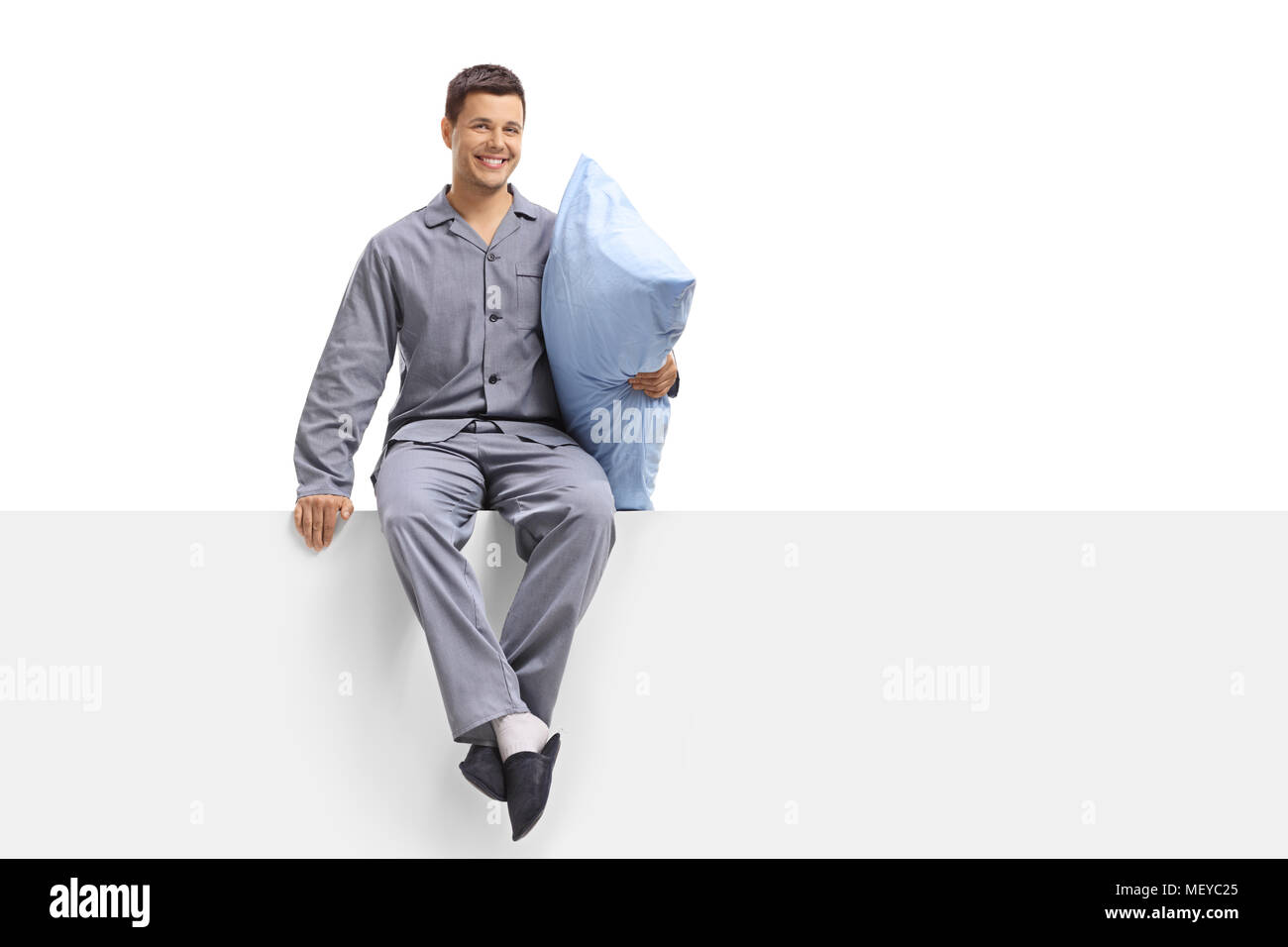 Young man in pajamas holding a pillow and sitting on a panel isolated on white background - Stock Image