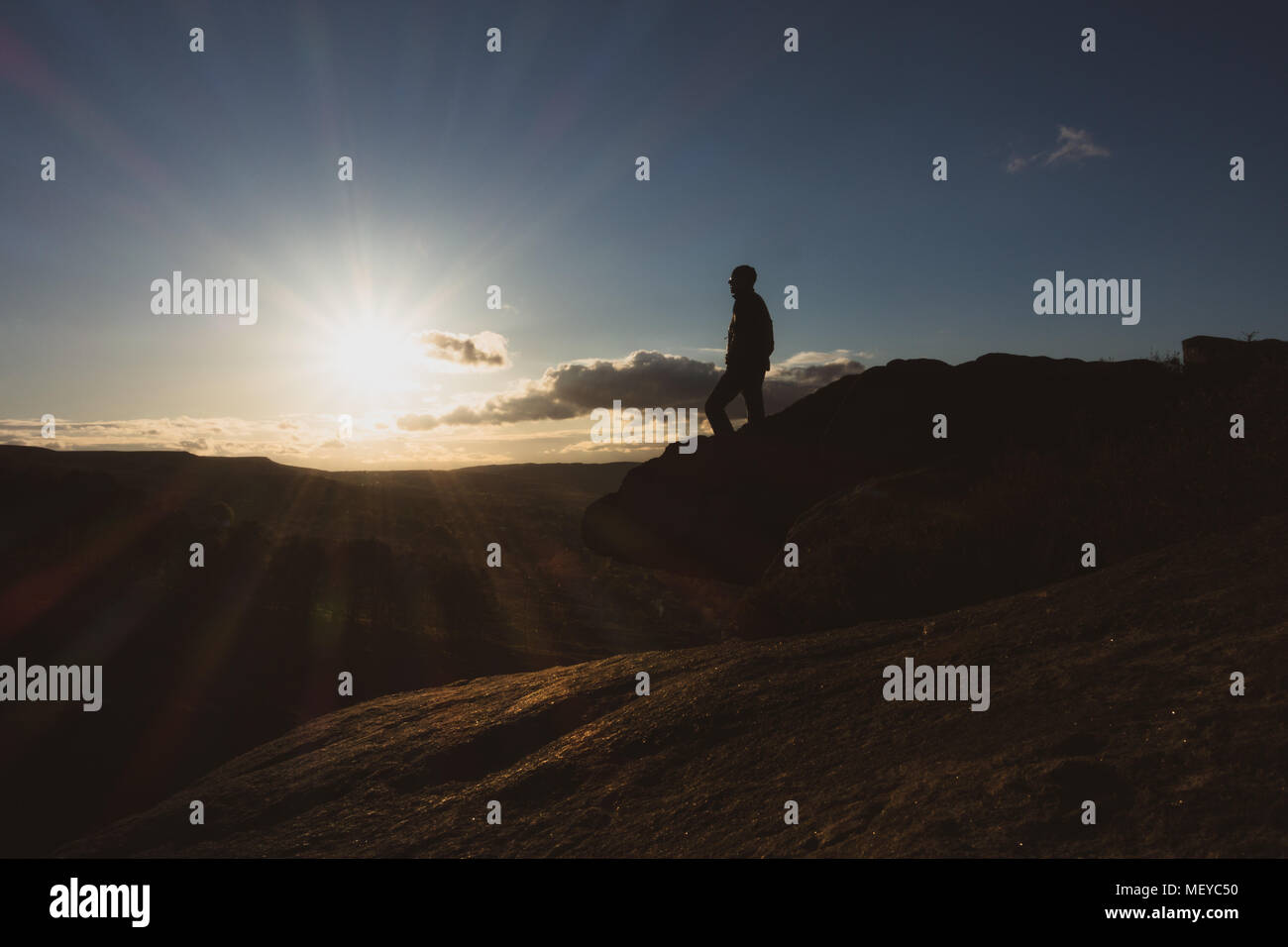 Man standing on the edge of a cliff (Crocodile Rock on Ilkley Moor) watching the sunset, UK - Stock Image