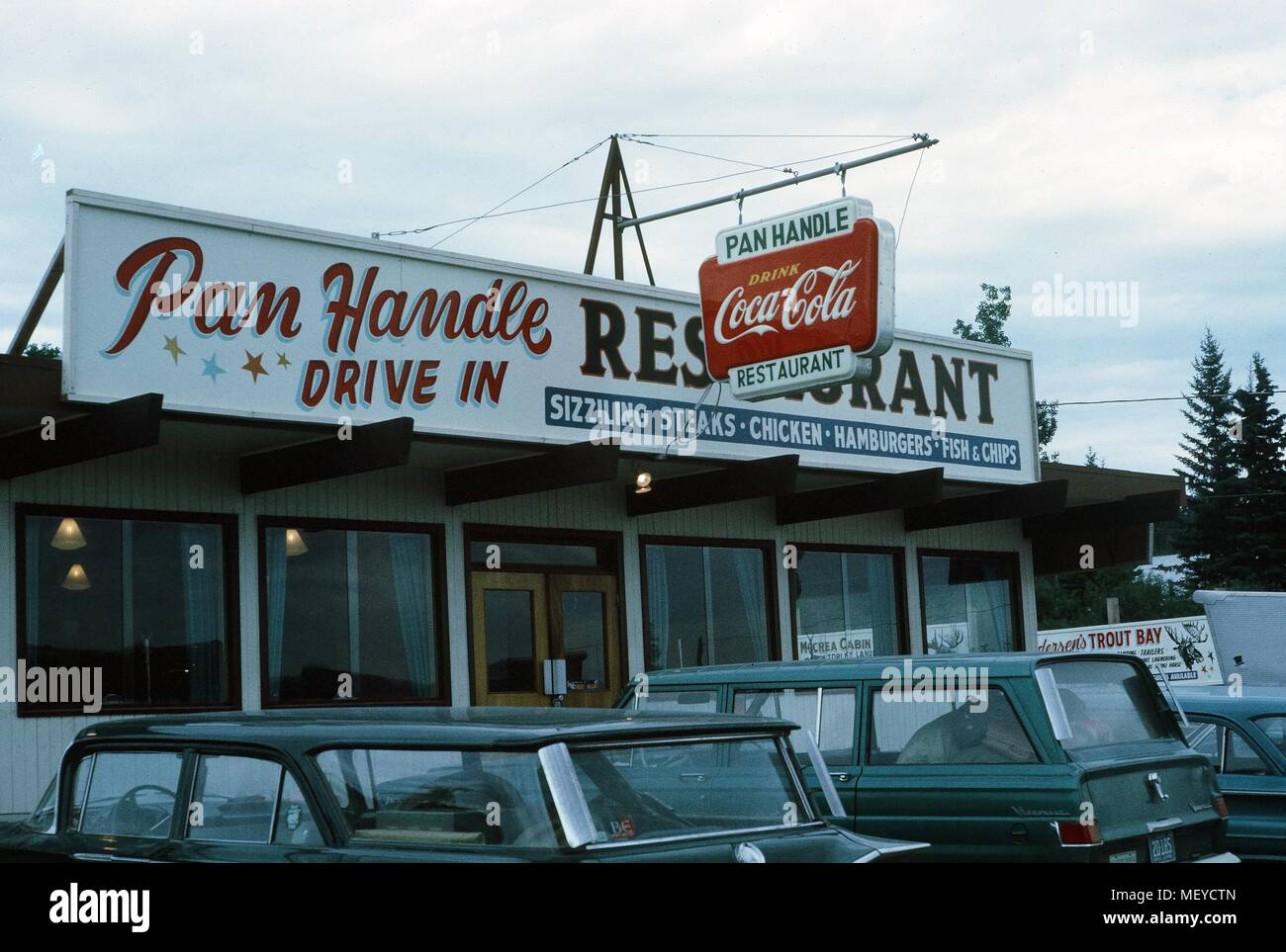 Facade of a classic American drive in restaurant, the Pan Handle Drive In, with cars parked outside and a sign for Coca Cola visible, United States, 1965. () - Stock Image