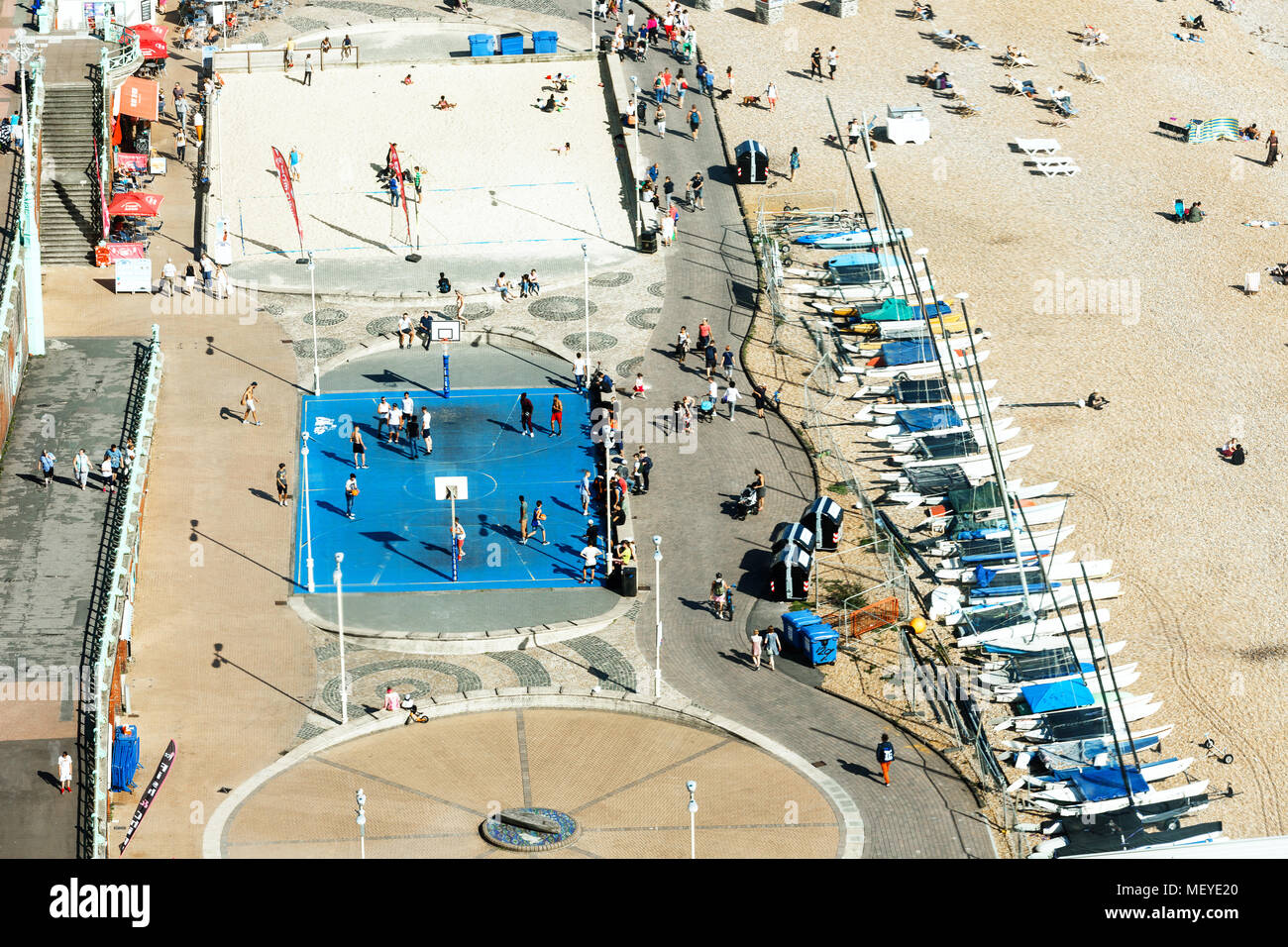 Aerial view of Brighton, people play basketball on court , parking for yachts - Stock Image