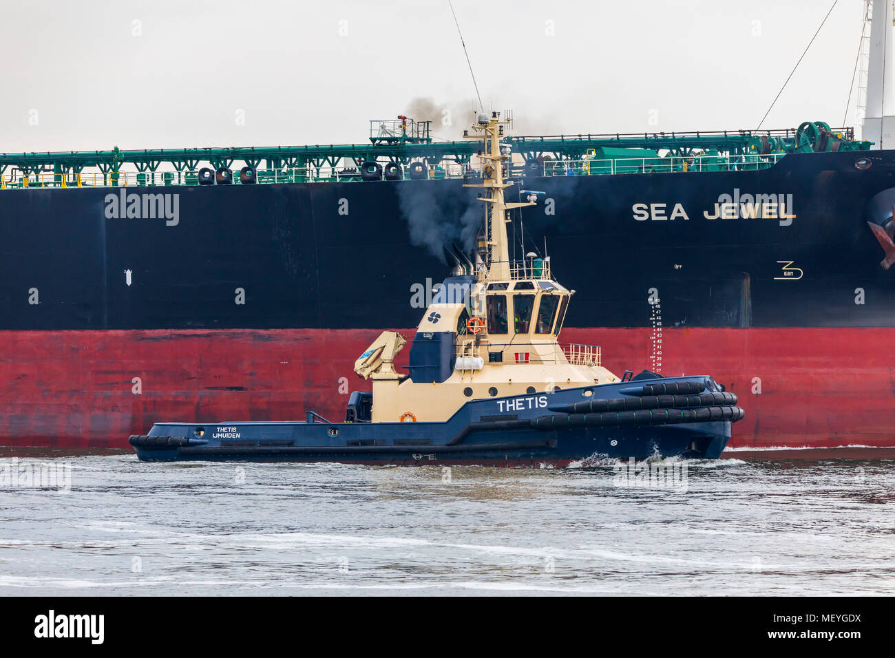 Crude oil tanker A.M.P.T.C-Sea Jewel, entering the port of Ijmuiden, in North Holland, Netherlands, tugboat, - Stock Image