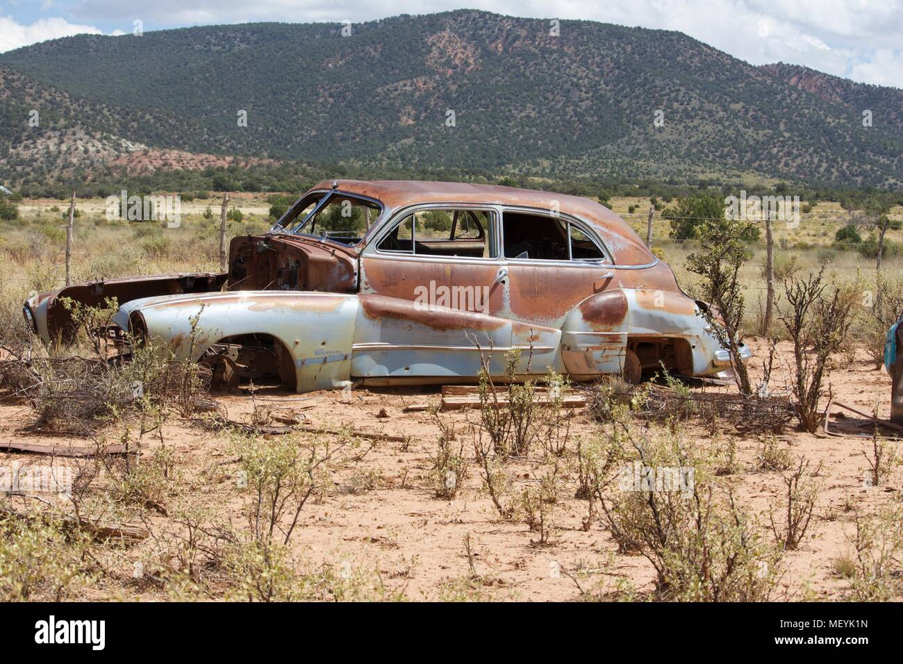 Abandoned rusty car in the desert surrounded by thin bushes. Gran Canyon National Park, USA - Stock Image