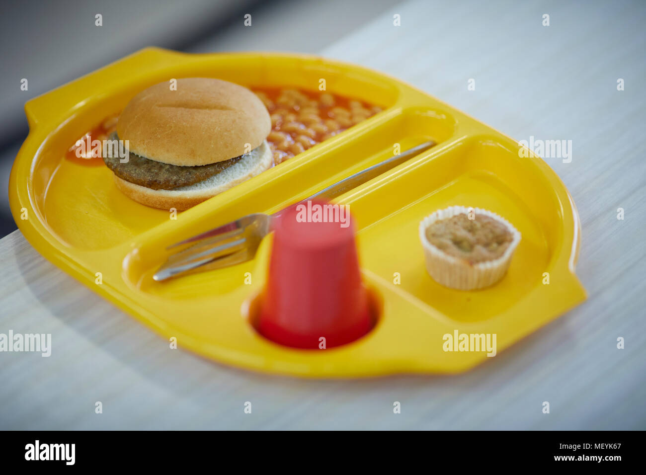 A school dinner meal tray with burger, beans, cake and drink Stock Photo