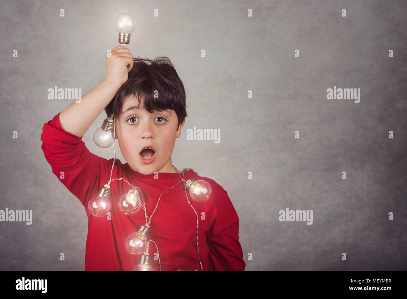 surprised boy with light bulbs on gray background - Stock Image