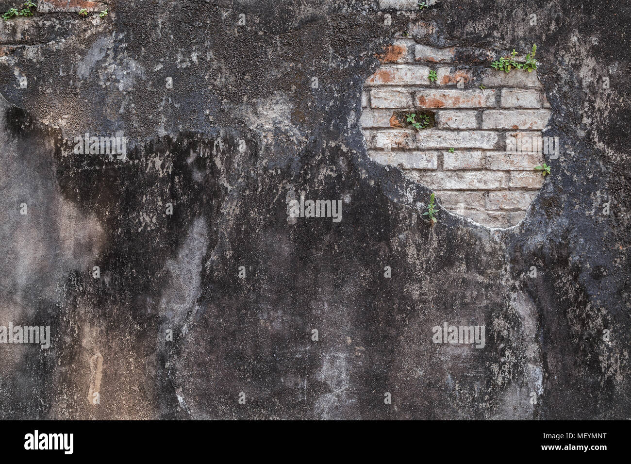 Full frame background of a weathered and damaged dark gray plastered wall. Plaster is partly peeled off revealing old bricks. Stock Photo