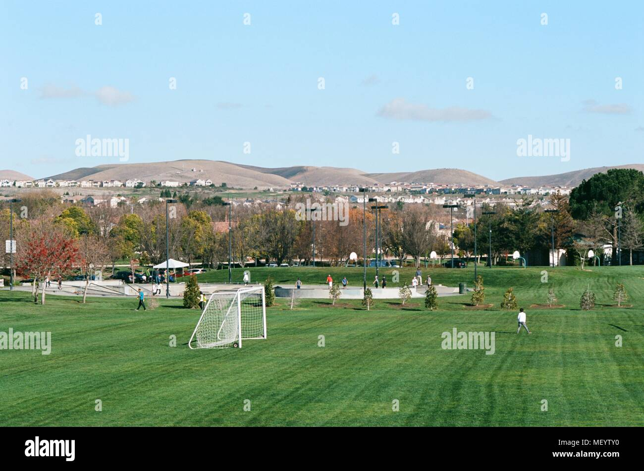 People play soccer at Emerald Glen park, with new housing visible in the background, a public park in the rapidly-developing San Francisco Bay Area city of Dublin, California, January 4, 2018. () - Stock Image