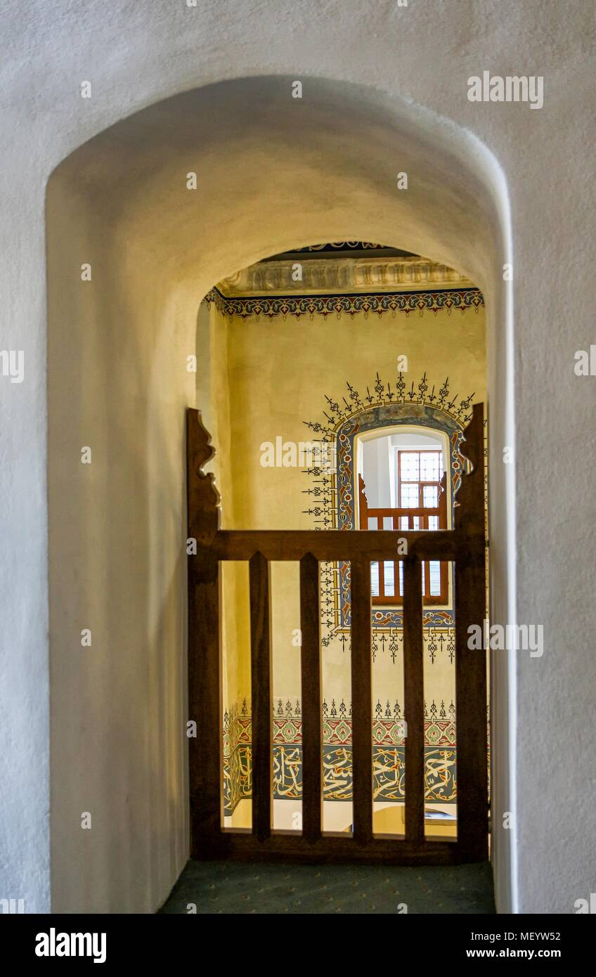 Photograph of a view through a vaulted opening with a wooden fence, looking over to a symmetrically corresponding opening across, with a decorative frame painted around it, in the upper parts of the gallery in the Little Hagia Sophia Mosque in Istanbul, Turkey, November 10, 2017. () - Stock Image