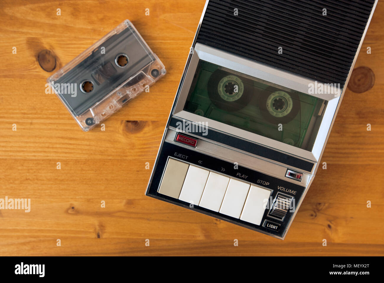 Audio cassette tape rolling in vintage player on the desk, top view. Police interrogation sound recording retro technology concept for 1970s, 80s and  Stock Photo