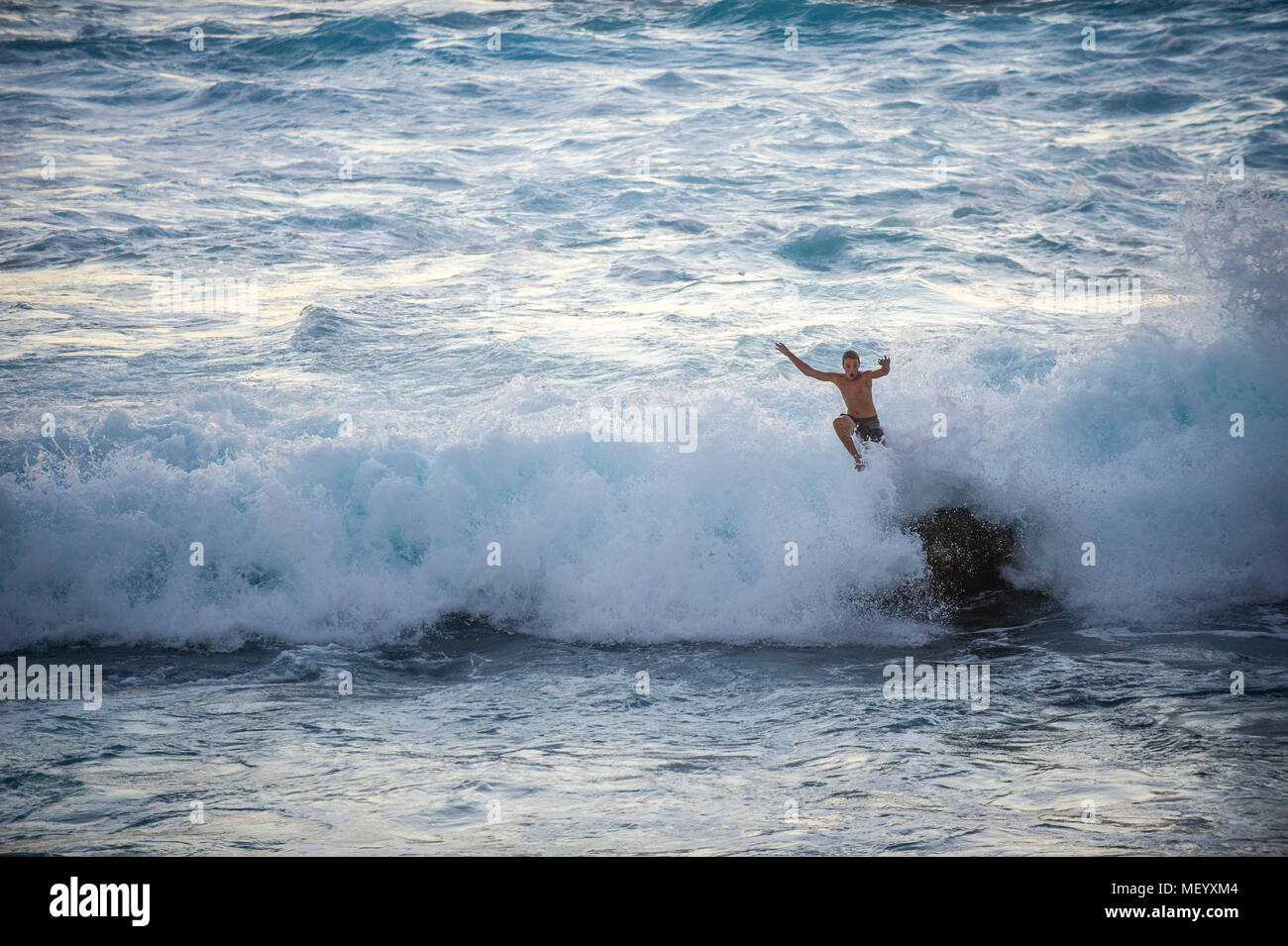A young man jumps into a wave at the Pointe au Sel on Réunion Island in the Indian Ocean. - Stock Image