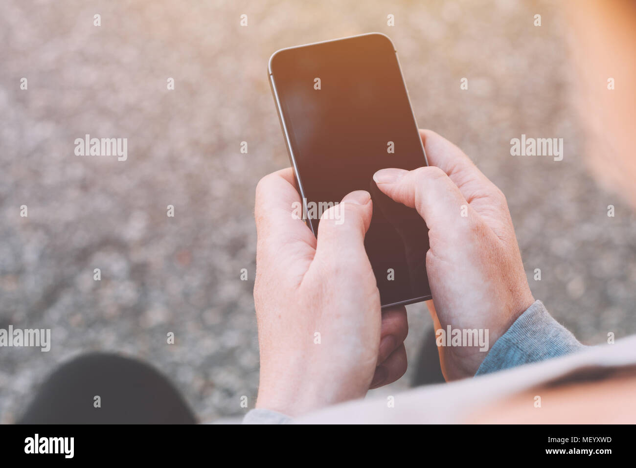 Close up of female hands using smartphone outdoors. Woman in sportswear tapping touch screen of mobile phone. - Stock Image