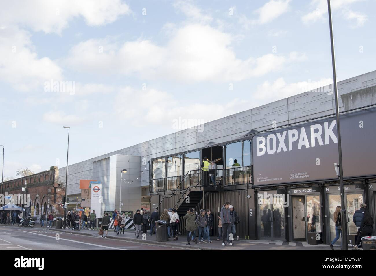 Shoppers walk through Boxpark, a pop-up shopping mall for fashion items constructed from recycling intermodal shipping containers, London, United Kingdom, October 29, 2017. () - Stock Image