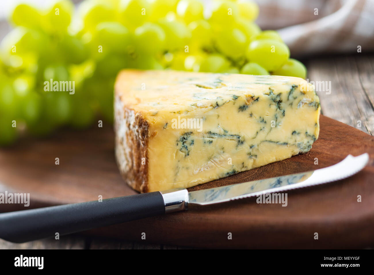 Tasty blue cheese with grapes on cutting board. - Stock Image